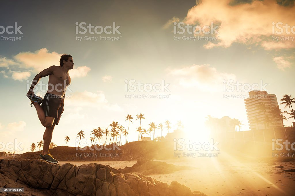 musculated brazilian does gymnastics at beach at sunset stock photo