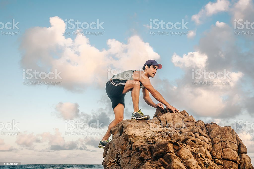 musculated man climbing up a rock under dramatic sky stock photo