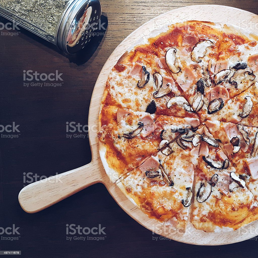 Mushroom and Ham Pizza in dark tone stock photo