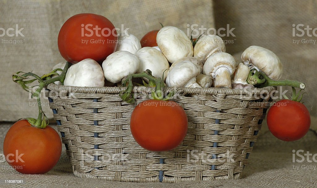 Mushrooms and tomatos in a basket stock photo