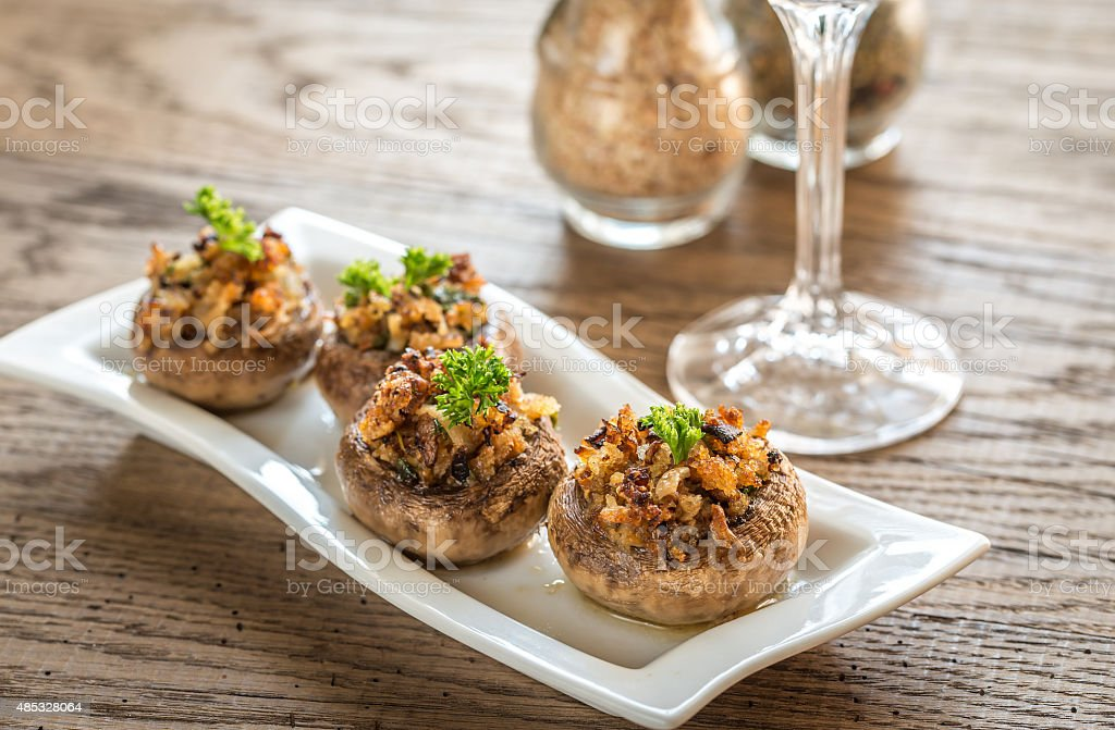Mushrooms' caps stuffed with cheese, onion, breadcrumbs and butter stock photo