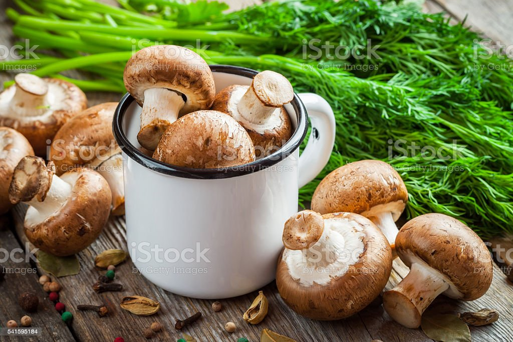 Mushrooms champignons in mug, dill and spices on table. stock photo