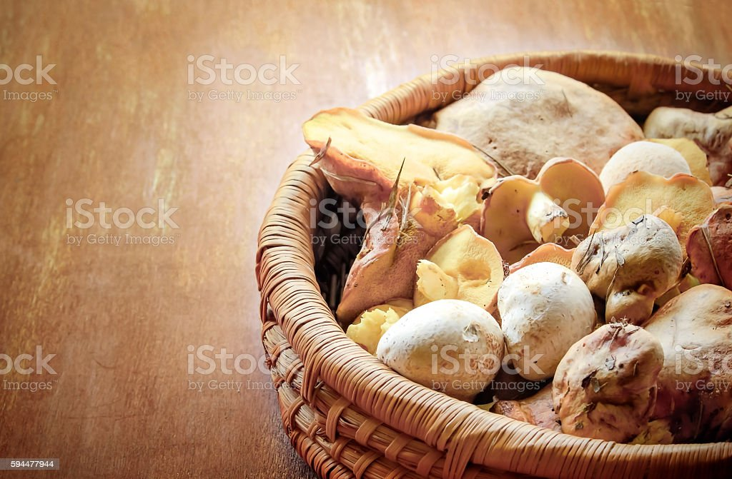 Mushrooms in a basket on wooden surface stock photo