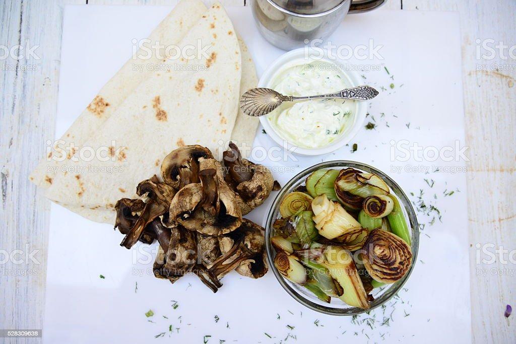 Mushrooms roasted with leek and yogurt sauce stock photo