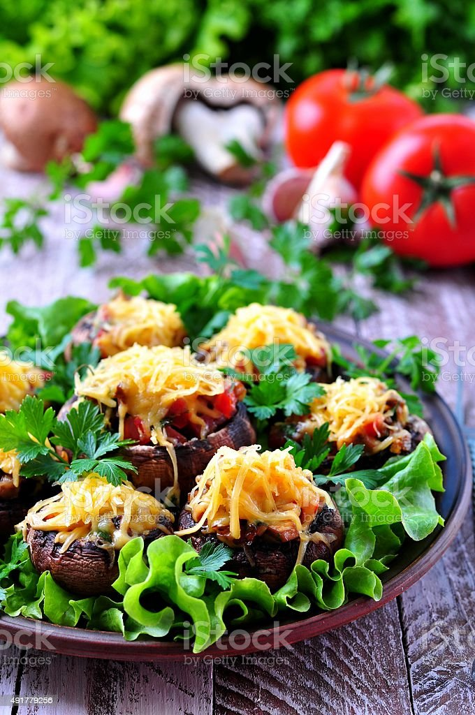 mushrooms stuffed with vegetables and bacon, baked with cheese stock photo