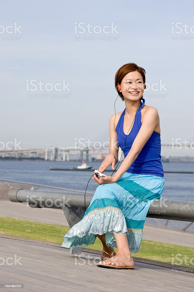 Music and a smile (Japanese woman) royalty-free stock photo