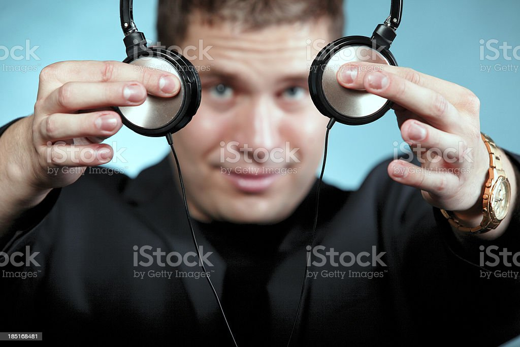 music and technology, smiling man offering headphones stock photo