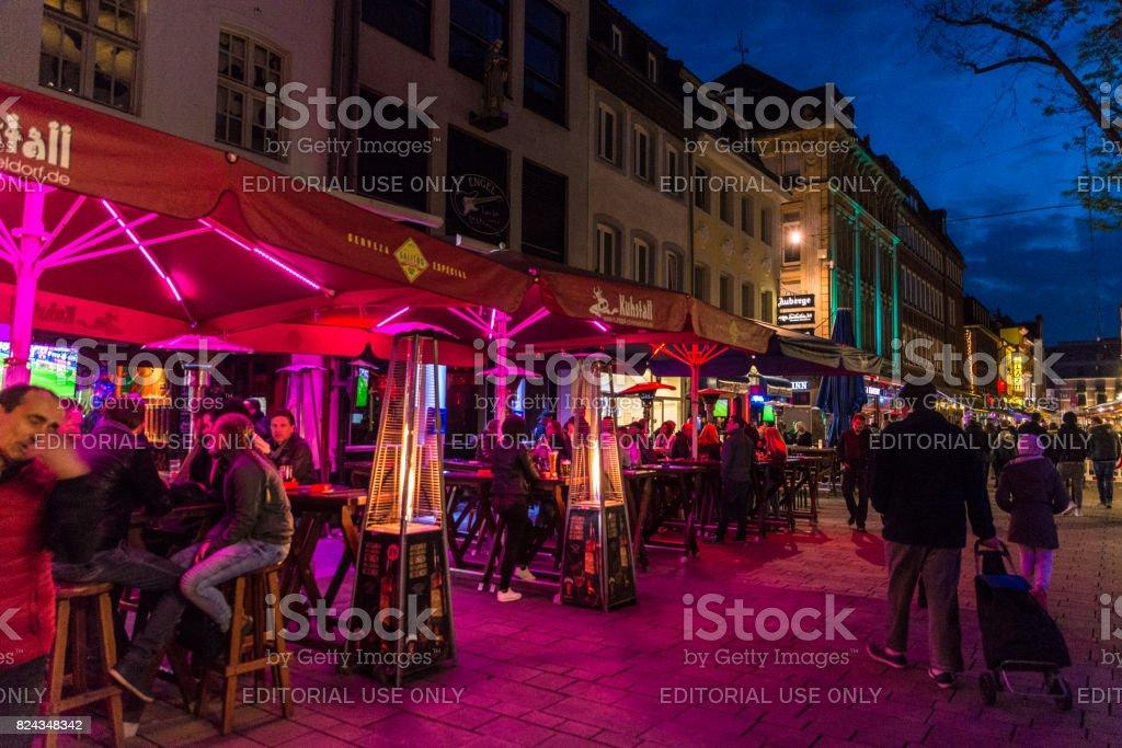 People enjoy music bars and restaurants at night in Altstadt of...