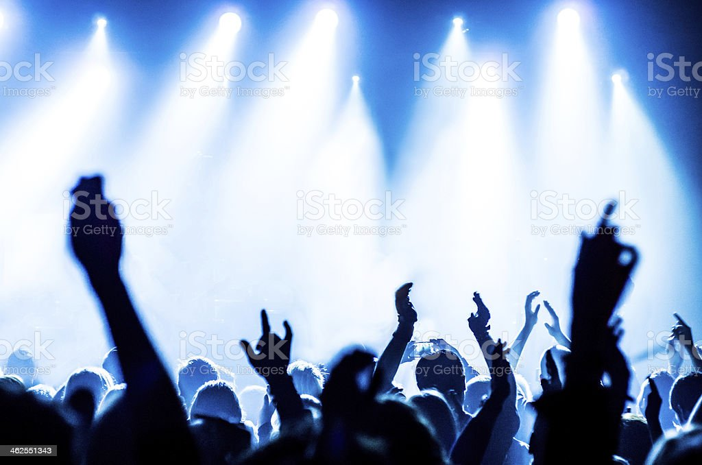various people in a concert with hands up and blue lights