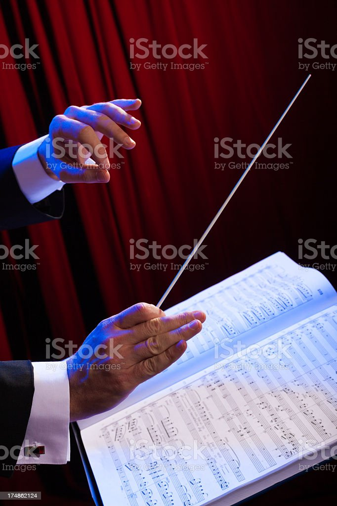 Music conductor holding a baton stock photo