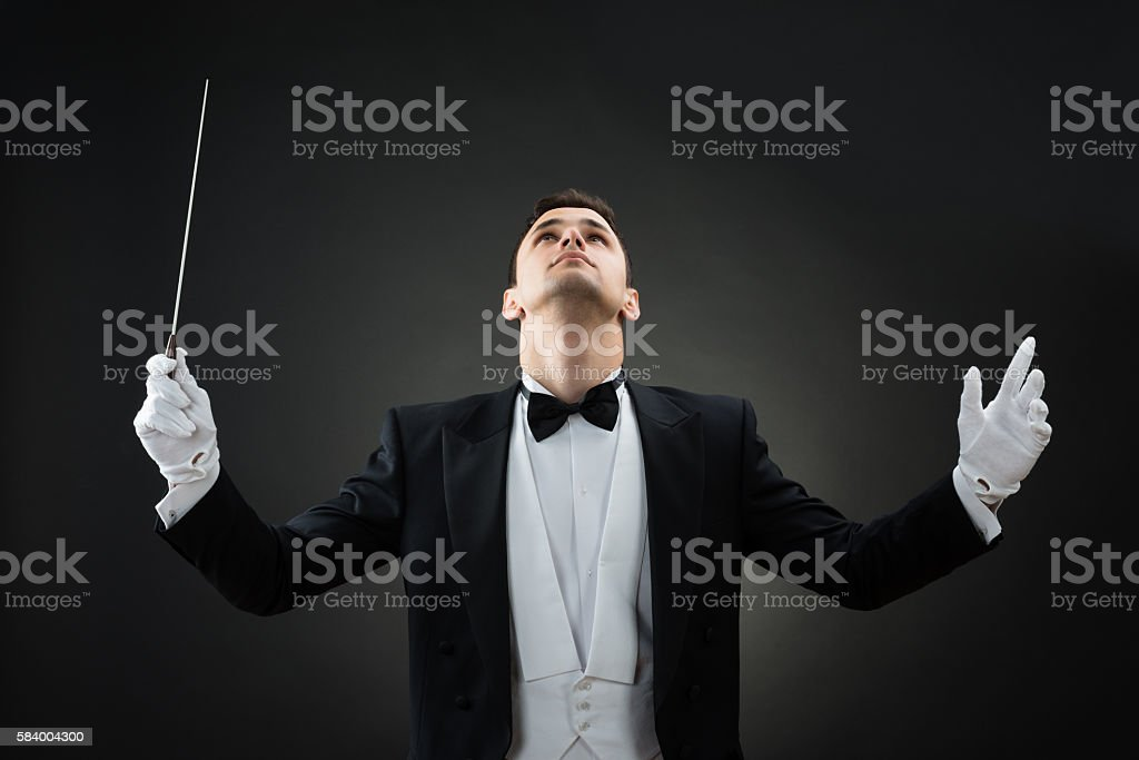 Music Conductor Looking Up While Holding Baton stock photo