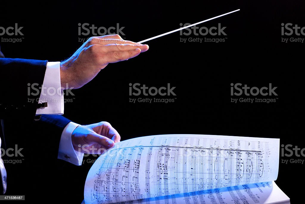 Music conductor using stick and turning the sheet music page stock photo