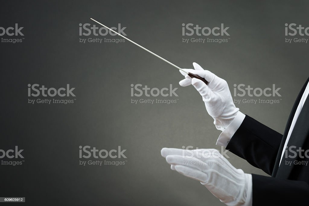 Music Conductor's Hand Instructing With Baton stock photo