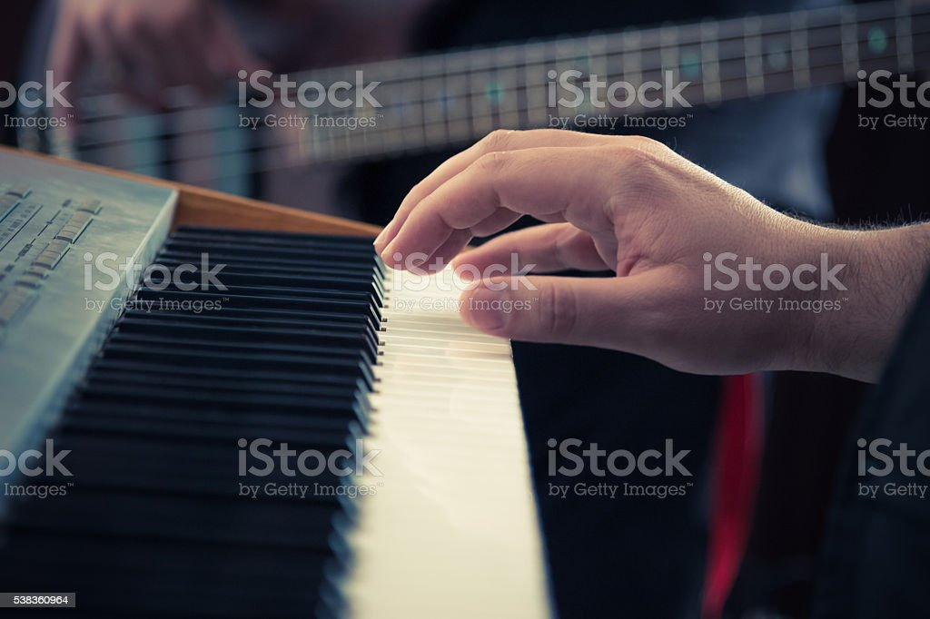 Music keyboard and bass guitar players close up stock photo