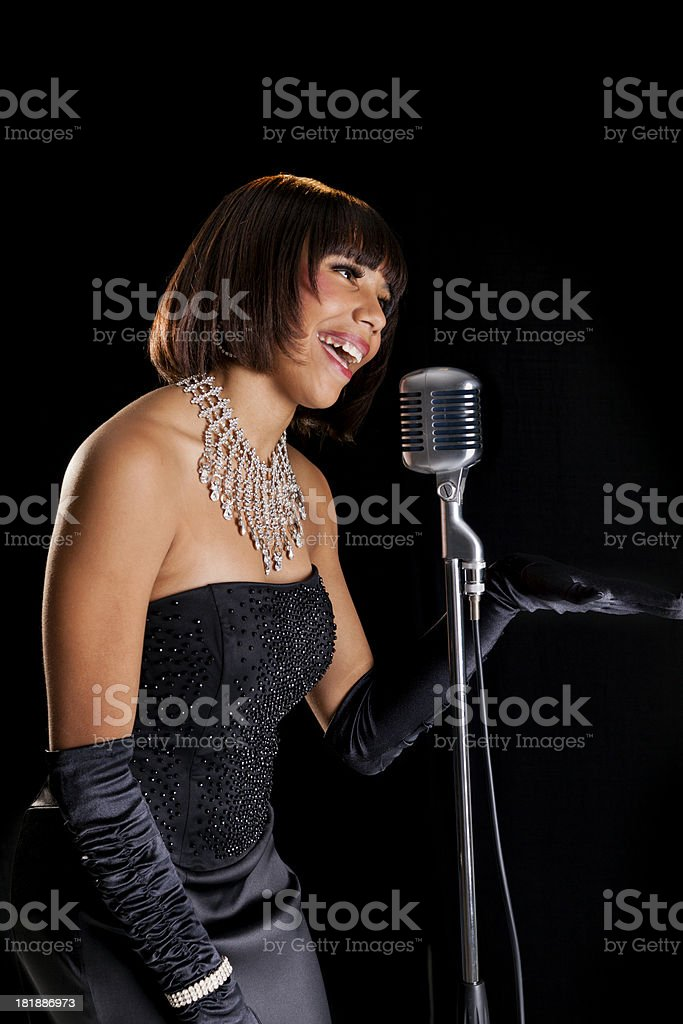 Music:  Lovely young lady in evening gown entertaining audience. royalty-free stock photo