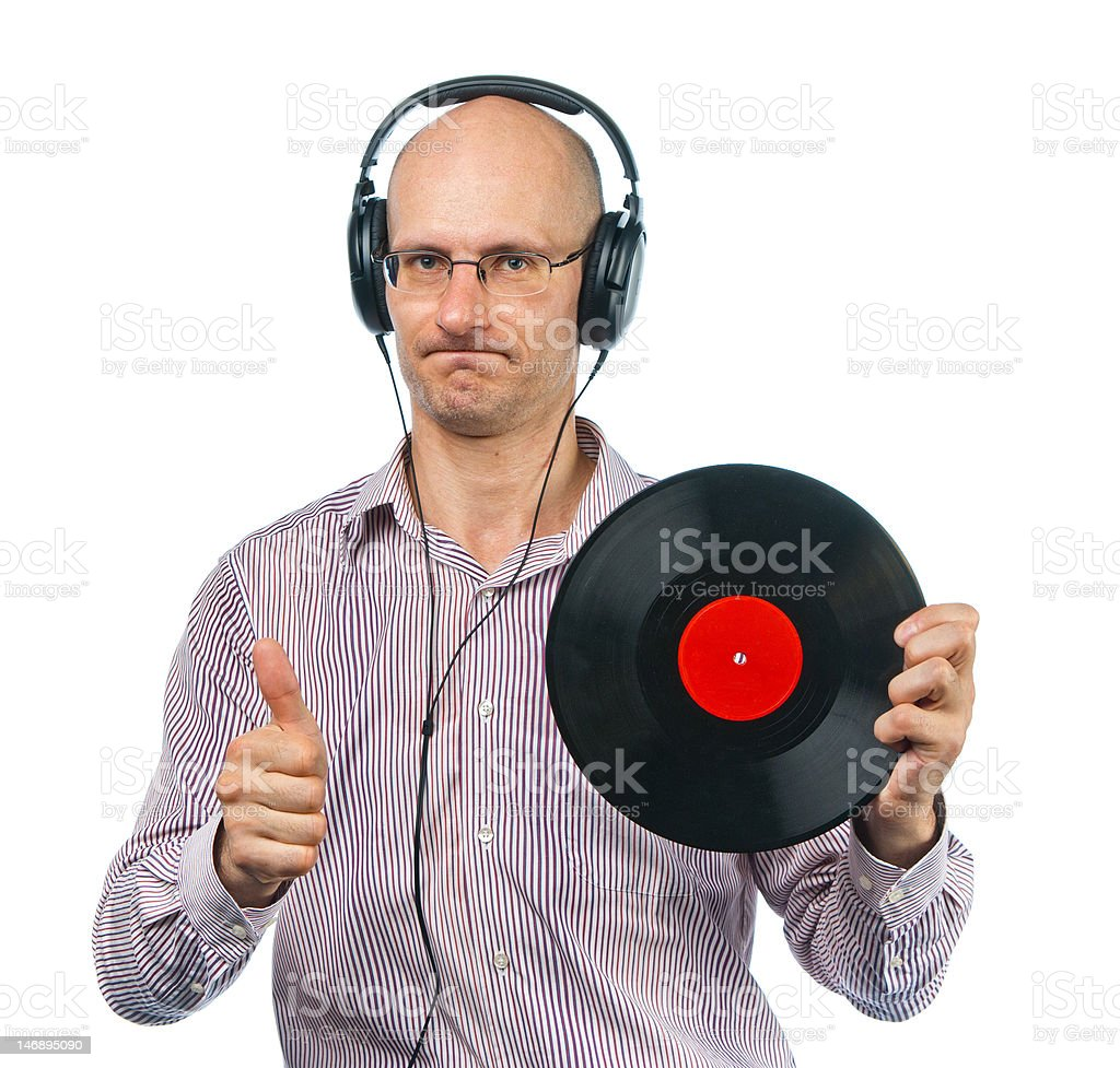 Music lover in headphones shows old disc royalty-free stock photo