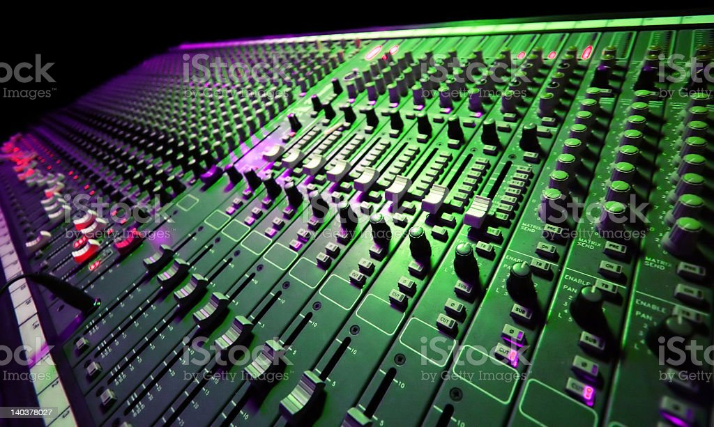 A music mixer table with a lot of switches, knobs, and dials stock photo