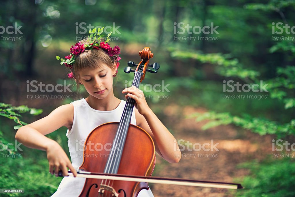 Music of nature - little cellist playing in beautiful forest stock photo