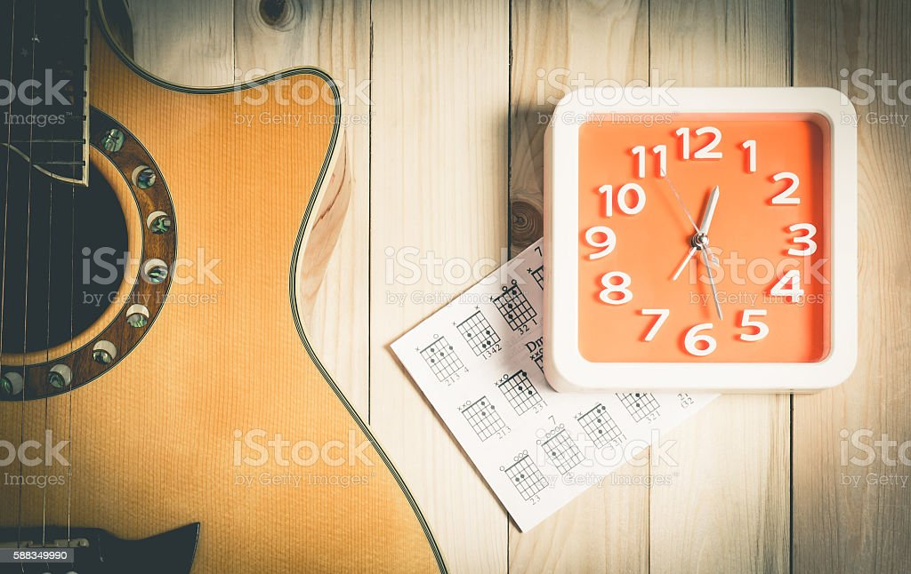 Music Practice time concept with acoustic guitar and wall clock stock photo