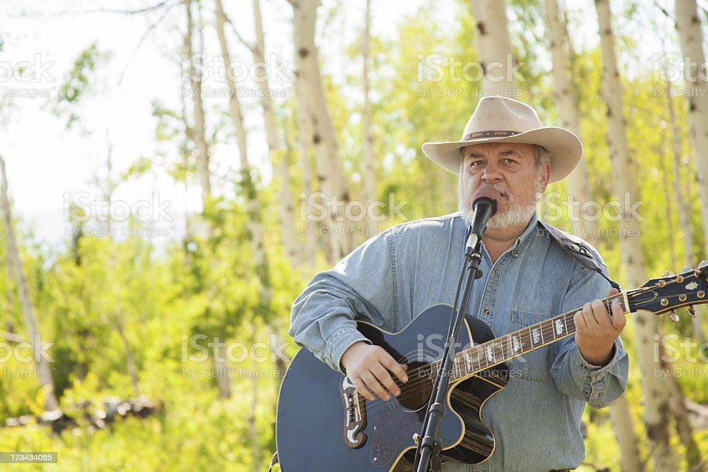 Music: Senior man sings, plays guitar at outdoor BBQ royalty-free stock photo