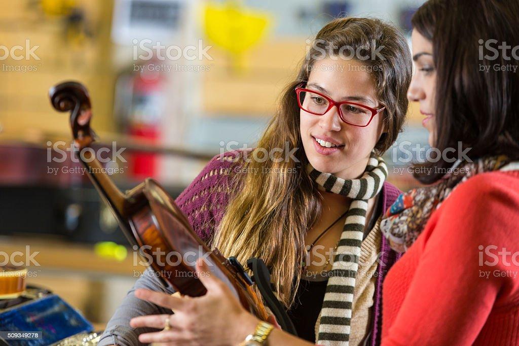 Music shop employee selling a violin to local musician stock photo