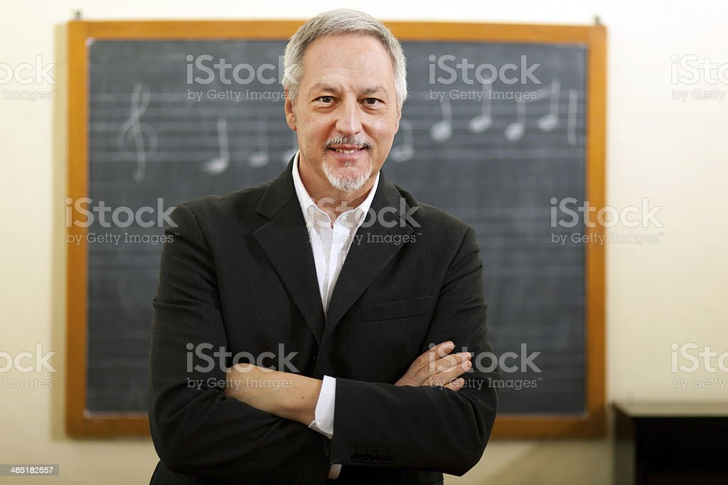 A music teacher standing in front of a chalkboard stock photo