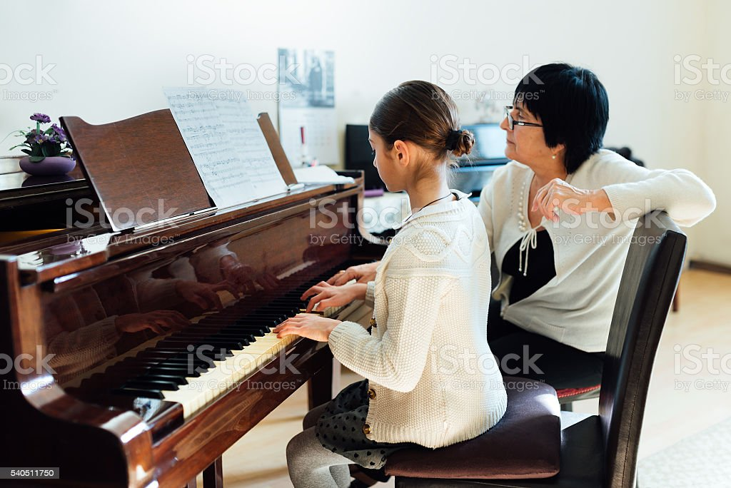 music teacher with the pupil at  lesson piano stock photo