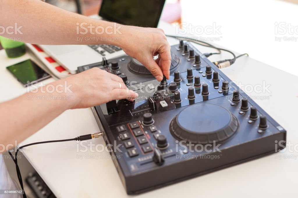 music technology, holiday party concept - male hands of Dj mixes audio track, beautiful black hi end disc jockey mixing device, digital concert equipment, resort entertainments, selective focus stock photo