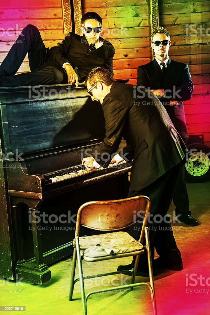 Music: Three men, black suits. Playing piano in nightclub. Security. stock photo