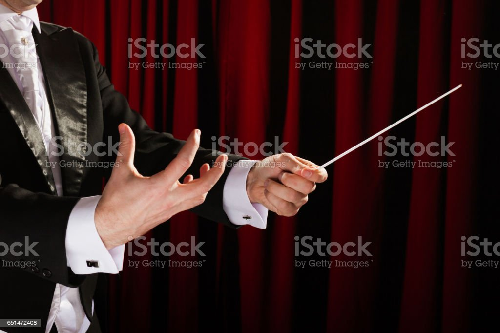 Musical conductor with a baton stock photo