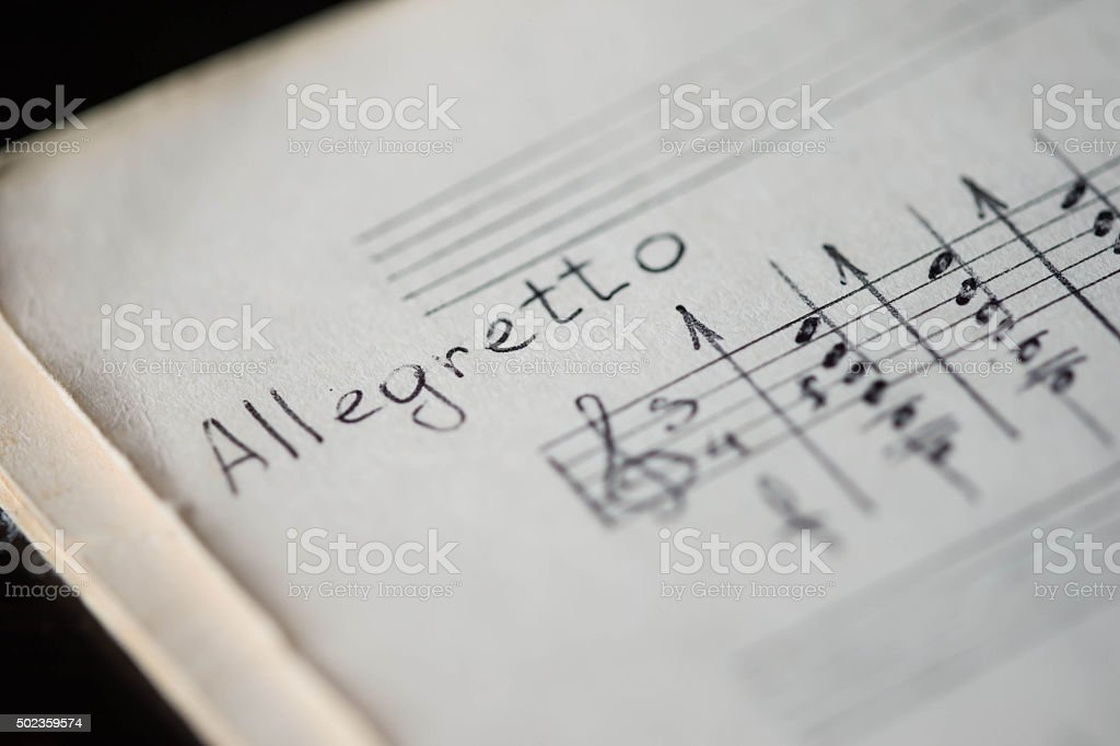 Musical tempo 'Allegretto' in a music book with hand-written notes stock photo