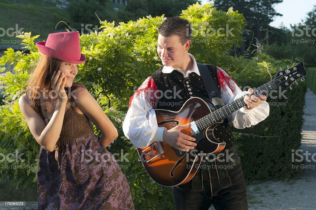 Musician Courting Woman with Pink Hat Slovenia stock photo