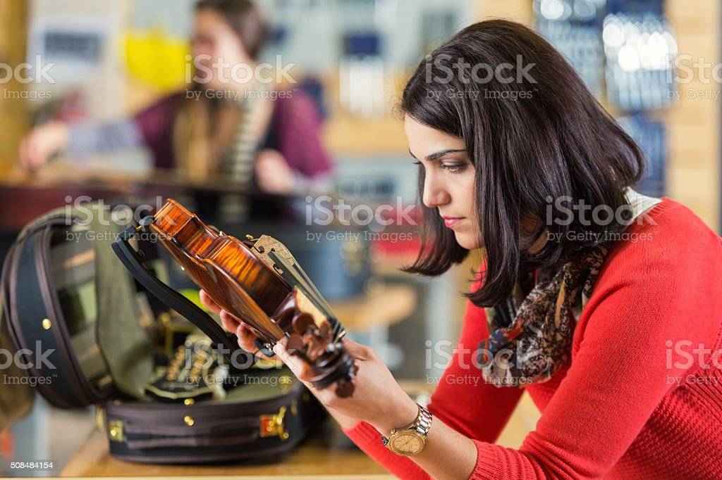 Musician examining violin she's purchasing in local musical instrument shop stock photo