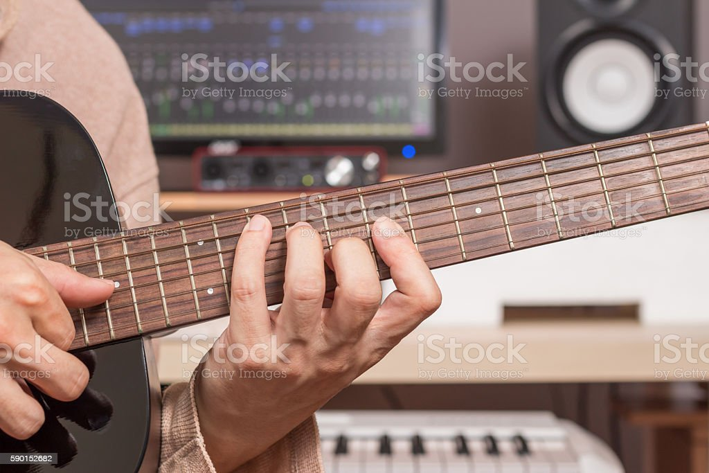 musician hands playing acoustic guitar in recording studio stock photo