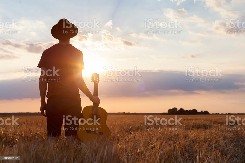 Musician holding acoustic guitar and walking in summer fields, sunset stock photo