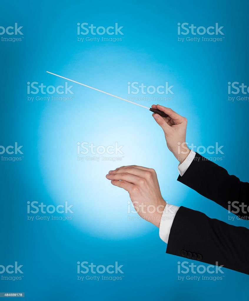 Musician Holding Baton Against Blue Background stock photo