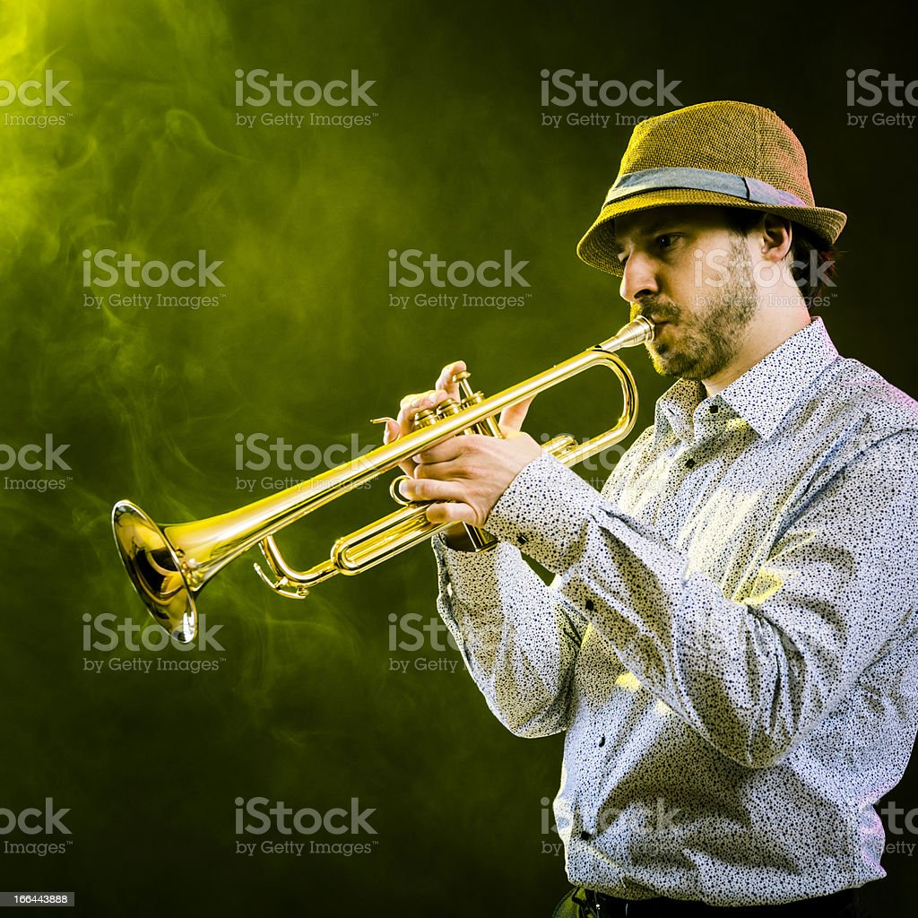 Musician is playing on the trumpet on stage, side view royalty-free stock photo