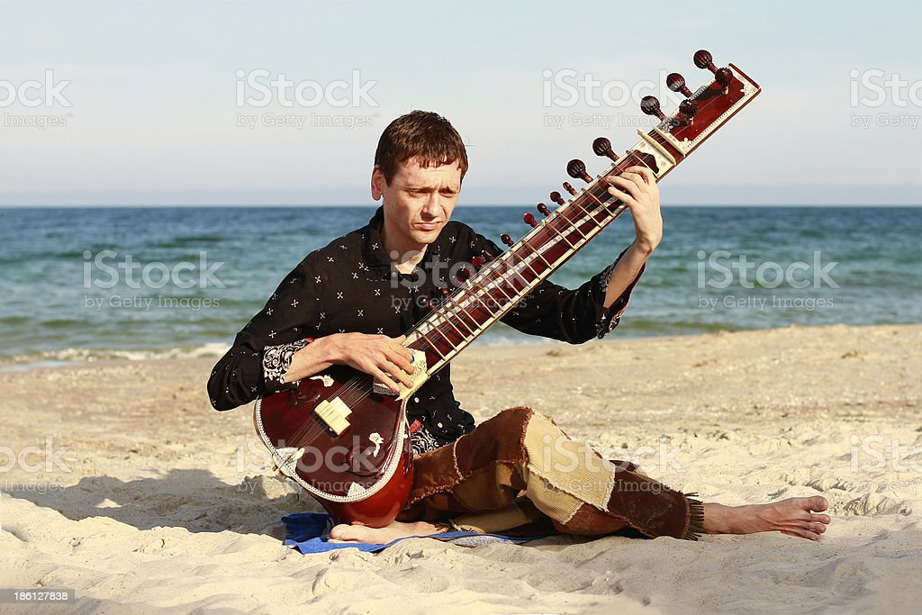 Musician is playing sitar on the beach stock photo