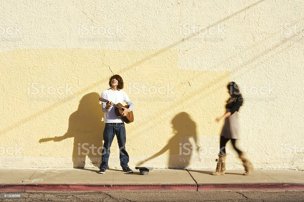 Musician on Sidewalk and Woman Pedestrian royalty-free stock photo