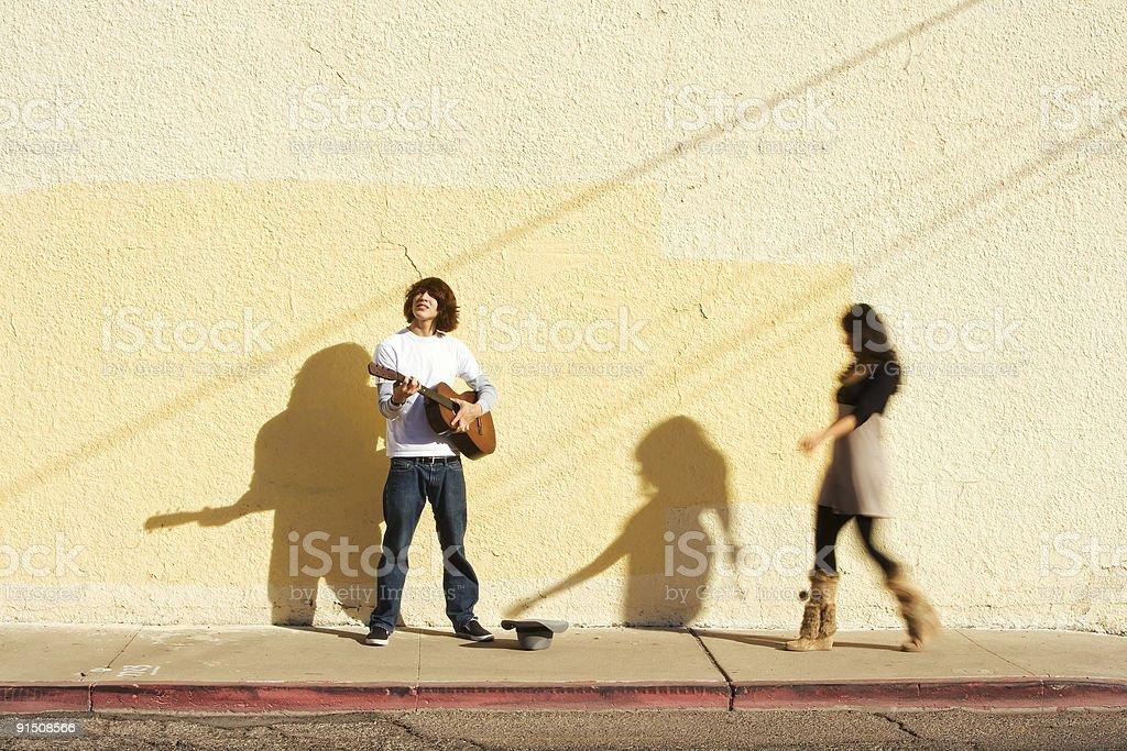 Musician on Sidewalk and Woman Pedestrian stock photo