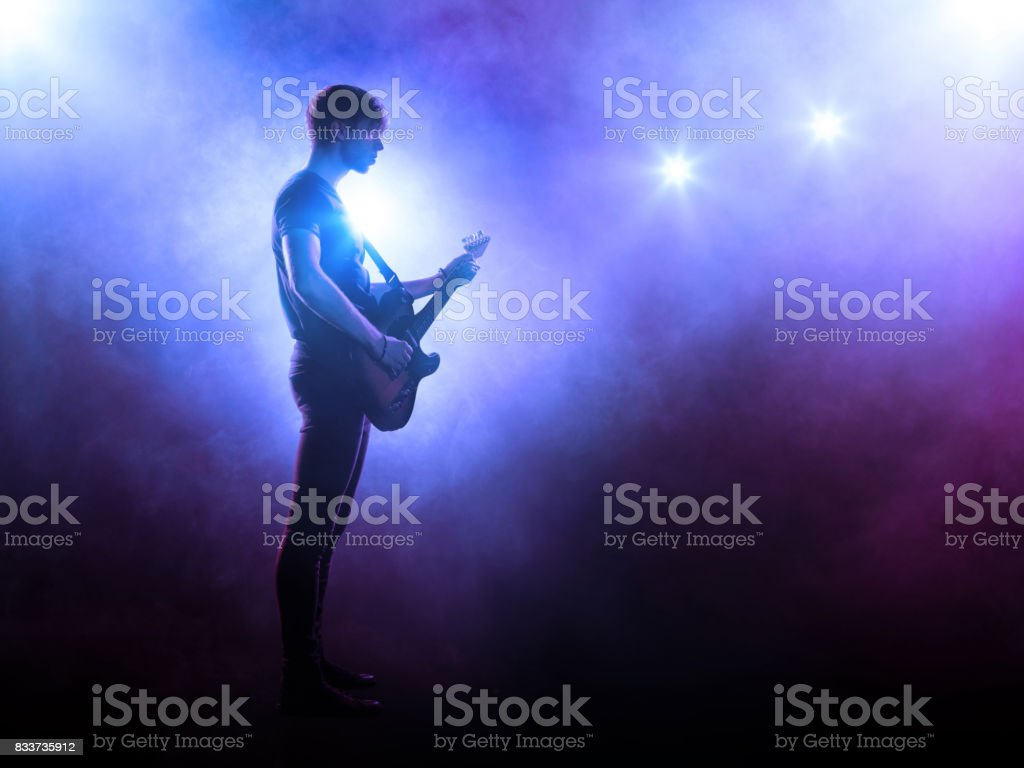 Musician performing on stage with a guitar stock photo