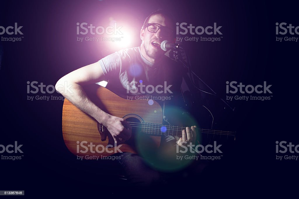 Musician playing acoustic guitar and singing stock photo