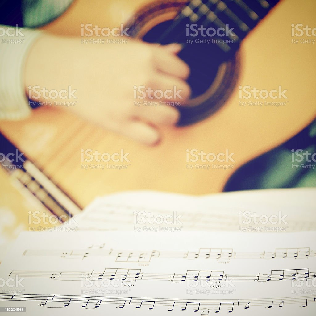 Musician playing classical guitar with musical chords royalty-free stock photo