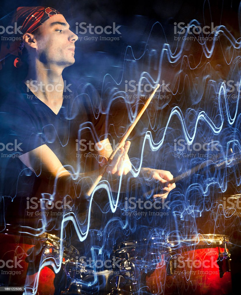 Musician playing drums in dark with pulsating light trace royalty-free stock photo