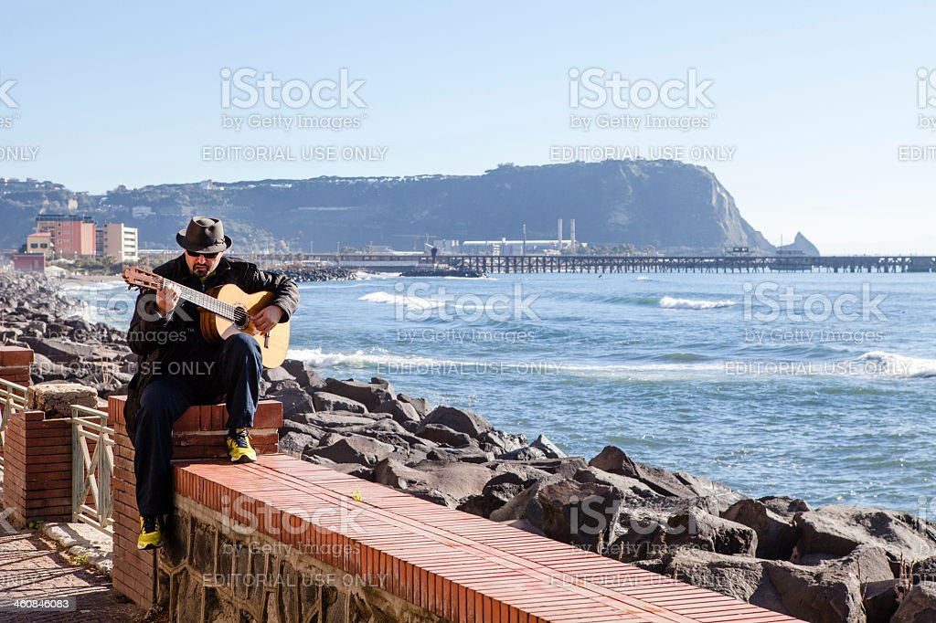 Musician Playing Guitar by the Sea royalty-free stock photo