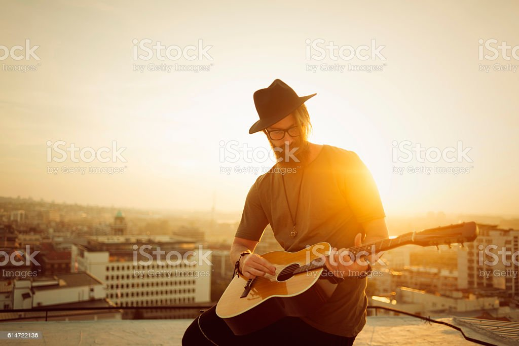 musician playing guitar on the roof stock photo