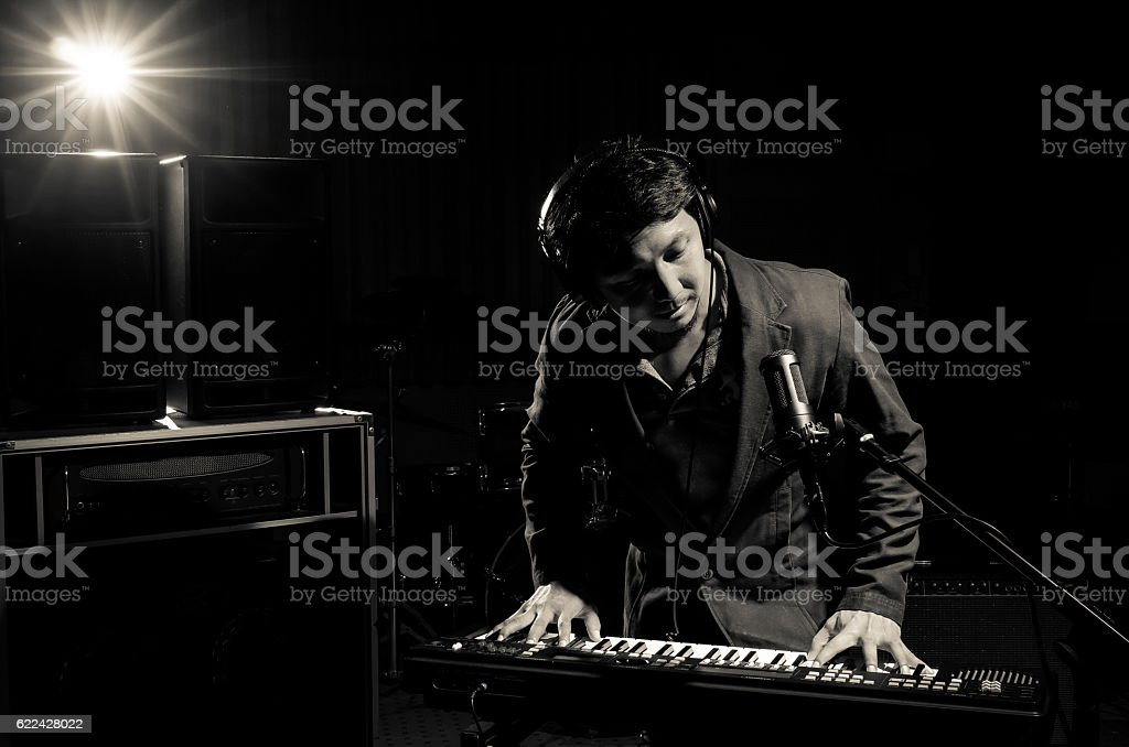 Musician playing keyboard with music instrument on dark backgrou stock photo