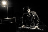 Musician playing keyboard with music instrument on dark backgrou