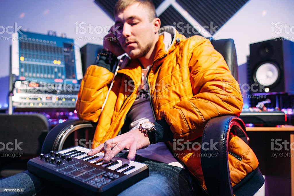 Musician playing on synthesizer at studio stock photo