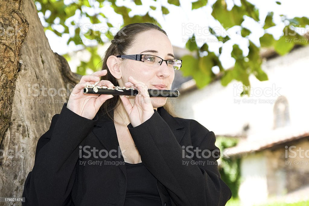 Musician playing piccolo in nature stock photo